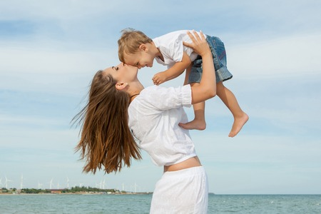 emotional love: Happy family. Young mother throws up baby in the sky, on sunny day. Portrait mother and little son on the beach. Positive human emotions, feelings, emotions. Stock Photo
