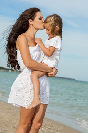beach kiss: Happy family. Young happy beautiful  mother and her little daughter hugging. Positive human emotions, feelings, emotions.