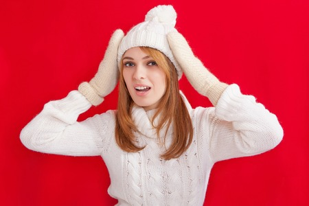 Beauty Girl wearing fashion white knitted hats and mittens. Winter cold  holiday. Woman in red background portrait. Surprise. photo