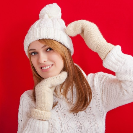 Beauty Girl wearing fashion white knitted hats and mittens. Winter cold  holiday. Woman in red background portrait. photo