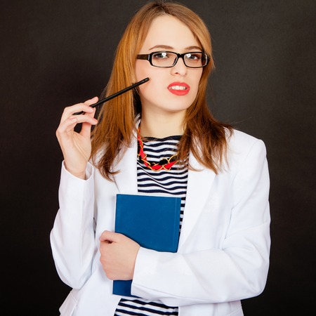 Fashionable doctor. Confident young female doctor in white uniform and glasses holding book and pencil while standing against black background photo