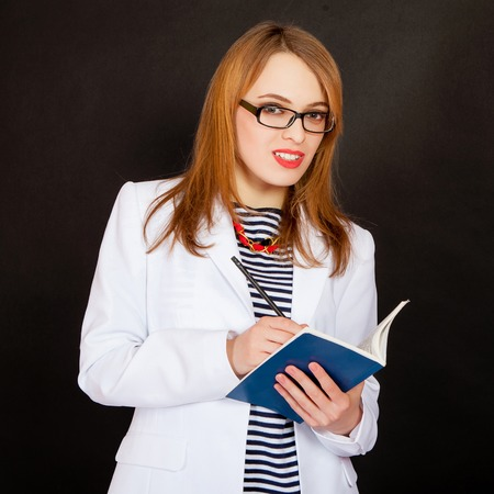 Fashionable doctor. Confident young female doctor in white uniform and glasses holding book and pencil and smiling while standing against black background photo