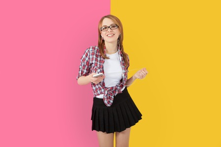 earbuds: Music. Woman dancing with earbuds  headphones listening to music on smartphone. Playful happy smiling young Caucasian woman isolated on yellow pink background.