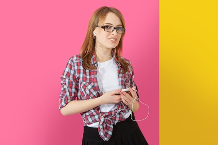 earbuds: Music. Woman with earbuds  headphones listening to music on smartphone. Playful happy smiling young Caucasian woman isolated on yellow pink background. Stock Photo