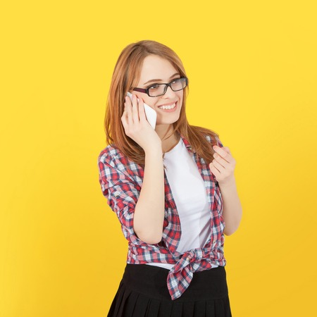 woman dialing phone number: Fashionable girl with glasses talking on mobile phone, yellow  background