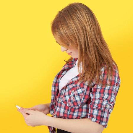 woman dialing phone number: Fashionable girl with glasses holding mobile phone in her hands, yellow background