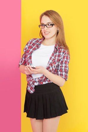 woman dialing phone number: Fashionable girl with glasses holding mobile phone in her hands, yellow pink background