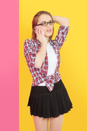 woman dialing phone number: Fashionable girl with glasses talking on mobile phone, yellow pink background Stock Photo