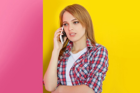 woman dialing phone number: Fashionable girl talking on mobile phone, yellow pink background Stock Photo