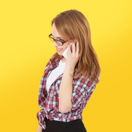 woman dialing phone number: Fashionable girl with glasses talking on mobile phone, yellow background Stock Photo