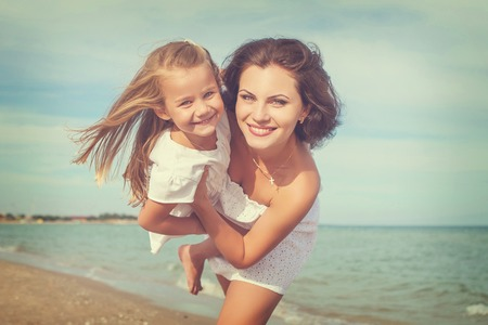 emotional love: Happy family. Young happy beautiful  mother and her daughter having fun on the beach. Positive human emotions, feelings, emotions.