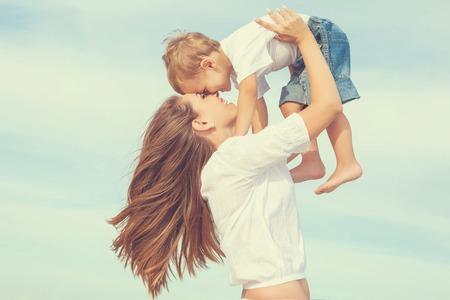가족: 행복한 가족. 젊은 어머니는 맑은 날에 하늘에서 아기를 던졌습니다. 해변에서 세로 어머니와 어린 아들. 긍정적 인 인간의 감정, 느낌, 감정.