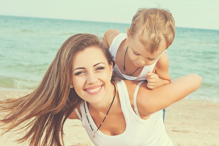 Happy family. Young happy beautiful  mother and her son having fun on the beach. Positive human emotions, feelings, emotions.