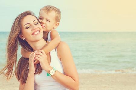 embrace family: Familia feliz. Hermosa joven madre feliz y su hijo se divierten en la playa. Las emociones positivas humanas, sentimientos, emociones. Foto de archivo
