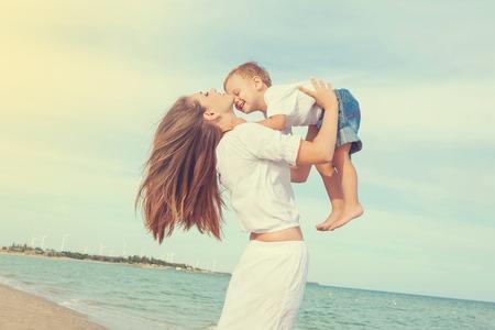 Gelukkig gezin. Jonge moeder gooit baby in de lucht, op zonnige dag. Portret moeder en zoontje op het strand. Positieve menselijke emoties, gevoelens, emoties. Stockfoto