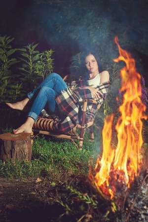 solitariness: Young pensive girl sitting near bonfire evening alone. Rest in a warm plaid.