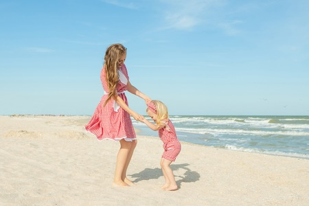 Happy family. Young happy beautiful  mother and her daughter  having fun on the beach. Positive human emotions, feelings, emotions.
