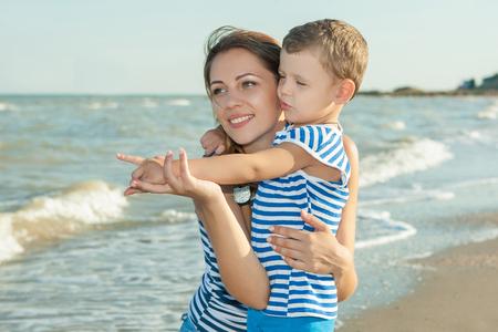 bebes niñas: Familia feliz. Hermosa joven madre feliz y su hijo se divierten en la playa. Las emociones positivas humanas, sentimientos, emociones. Foto de archivo
