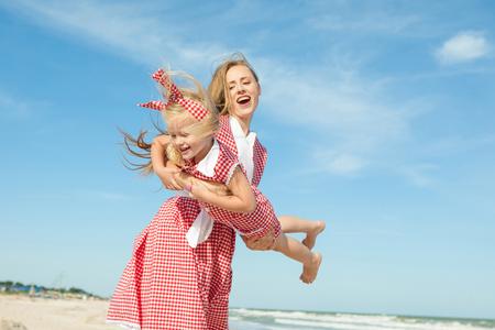 convivencia familiar: Familia feliz. Hermosa joven madre feliz y su hija que se divierten en la playa. Las emociones positivas humanas, sentimientos, emociones.
