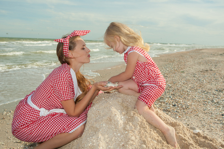 droll: Happy family. Young beautiful  mother and her daughter  having fun on the beach. Positive human emotions, feelings.