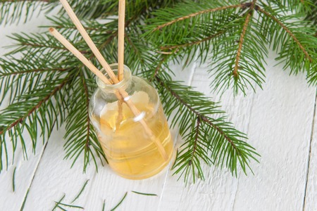 scent: Fragrance sticks or bottle Scent diffuser with sprig fir on wooden background. Stock Photo