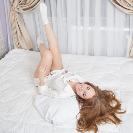 tired eyes: A woman lying, enjoying at of the bed  and smiling, with her long hair.