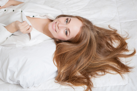 A woman lying, enjoying at of the bed  and smiling, with her long hair.