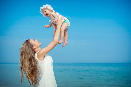 dia soleado: Familia feliz. Joven madre vomita bebé en el cielo, en un día soleado en la playa. Emociones humanas positivas, sentimientos.