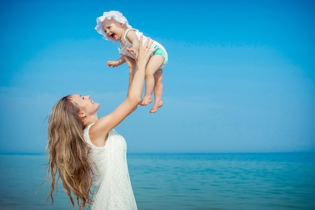 sunny sky: Happy family. Young mother throws up baby in the sky, on sunny day on the beach. Positive human emotions, feelings.
