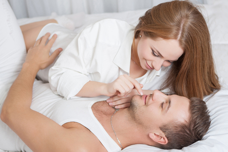 adult couple: Romantic young woman touching mans lips while lying in bed Stock Photo