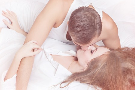 sex tenderness: Sexual scene of gentle and affectionate young couple in the bedroom