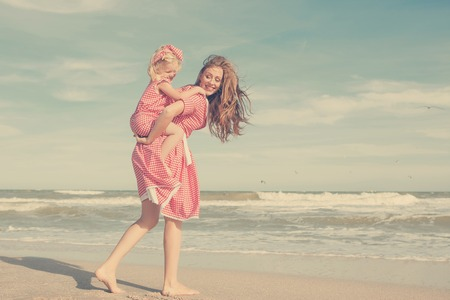 droll: Happy family. Young beautiful  mother and her daughter  having fun on the beach. Positive human emotions, feelings. Retro toned