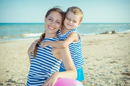 Familia feliz. Hermosa joven madre feliz y su hijo se divierten en la playa. Las emociones positivas humanas, sentimientos, emociones.