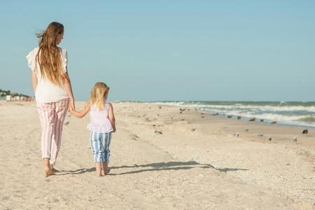 Familia feliz. Hermosa joven madre feliz y su hija que se divierten en la playa. Las emociones positivas humanas, sentimientos, emociones.