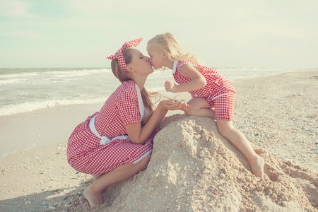 Happy family. Young beautiful  mother and her daughter  having fun on the beach. Positive human emotions, feelings, kiss.