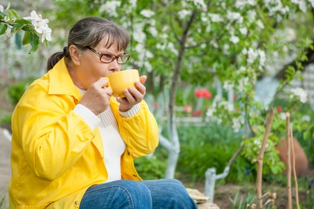 landlady: Woman in her garden resting sitting with cup tea