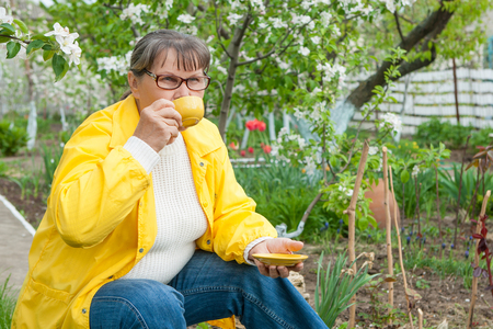 landlady: Woman in her garden resting sitting with cup coffee Stock Photo