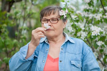 olfato: Mujer en su jard�n. Goza del olor de flores.