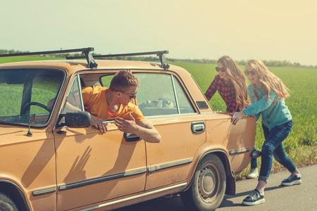 amigos inconformista jóvenes en viaje por carretera en un día de verano. rotura del motor down.Two niñas que empujan un coche de época, mientras que el hombre está envalentonando their.Travel, aventura, unforeseenteamwork, concepto divertido. retro tonificado