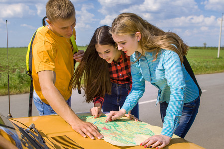 prettiness: Three friends wanderer with trendy look searching direction on location map on old car in summer, happy two girls and a guy tourist searching road to hotel or  direction  seaon atlas in country road Stock Photo