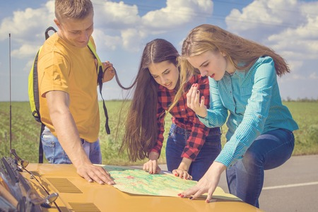astray: Three friends wanderer searching direction on location map on old car, two girls and  guy tourist searching road to hotel or direction seaon atlas in country road Stock Photo