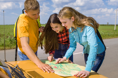 astray: Three friends wanderer with trendy look searching direction on location map on old car in summer, happy two girls and a guy tourist searching road to hotel or  direction  seaon atlas in country road Stock Photo