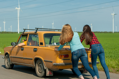 Young hipster friends on road trip on a summers day. Engine break down.Two girls pushing a vintage car while man is emboldening their.Travel, adventure, unforeseenteamwork, funny concept