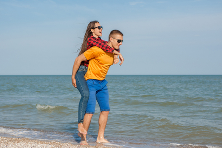 adolescents: Happy young joyful guy and girl having fun on the beach, laughing together. During summer holidays vacation on sea. Beautiful energetic couple friends adolescents.