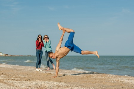 adolescents: Happy young joyful guy and two girls having fun on the beach, laughing together. During summer holidays vacation on sea. Beautiful energetic  friends adolescents. Stock Photo