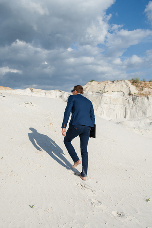 formalwear: Businessman on desert dune. Rear view of young man in formalwear rising up by sand mountain Stock Photo