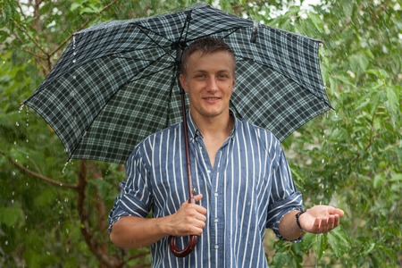 Young happy Man with umbrella in rainy weather. Summer day