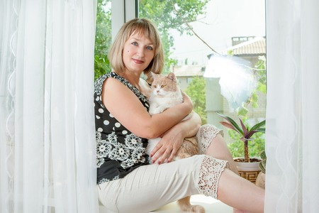 Adult  woman with cat sits on window in her apartment.