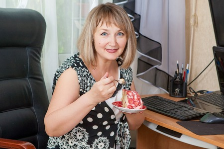 woman eating cake: Smiling adult woman eating cake at desk in her apartment. Break during work on computer