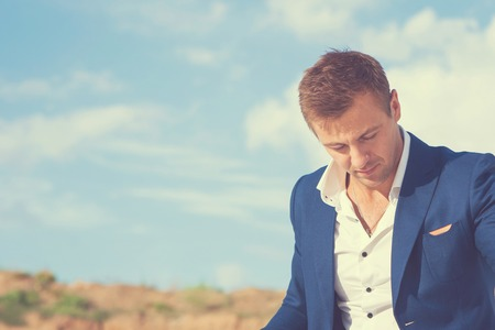 bowed head: Beautiful young man in formalwear outdoor enjoying nature and the sun. Peaceful place to leisure. With his head bowed and his eyes closed, pensive. Stock Photo